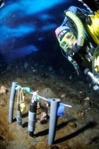 Jeffrey Bozanic under the Antarctic ice (blue background) inspecting temperature data loggers. Photo by Jeffrey Bozanic,