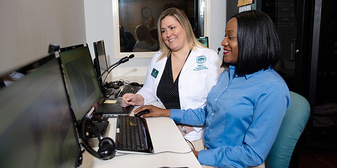 Article Feature Image of a Nurse working with a student at a computer