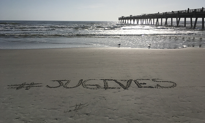 #JUGives written in the sand at the beach