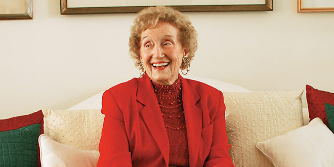 Dr. Frances Bartlett Kinne Smiling while sitting on a couch