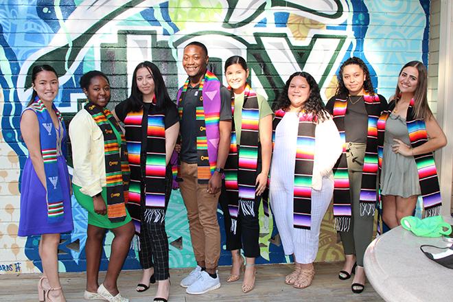 The following students standing in front of a wall. Kimmi Brostek, Zahria Green, Ana Estevez, Janard Curry, Nicol Torres, Yashohara Miranda, Myasia Reyes, Michelle Owen