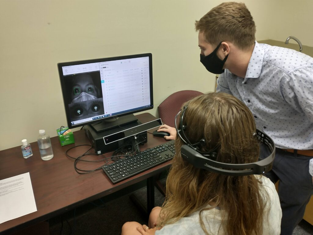 Hunter McVea working with a study participant on an EEG machine which is used to measure brain activity, and an eye tracker tracks eye movement while participants complete computer work.