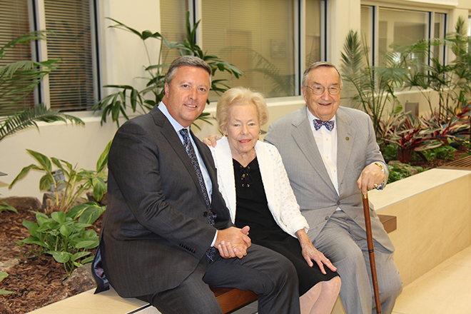 President Tim Cost, Carol Shircliff and Bob Shircliff sitting on wall and posing for a photo in 2015