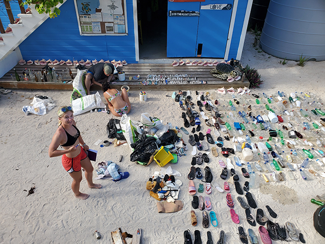 Photo of the results of a beach cleanup, showing many bottles and discarded shoes