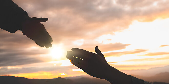 Silhouette of two hands reaching across a sunset