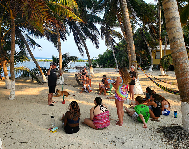 Photo of Dr. Jeremy Stalker teaching on the island of Tobacco Caye, using a broom and the sand as a chalkboard