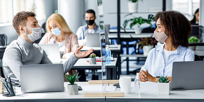 People interacting in an office work environment with COVID protections