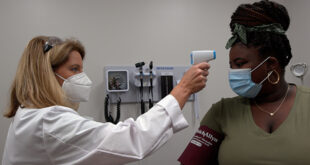 A nurse takes a woman's temperature