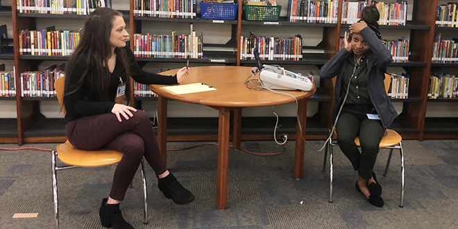 Allison Ventrone and fellow student Camisha Hatcher at a table in the library of a local elementary school